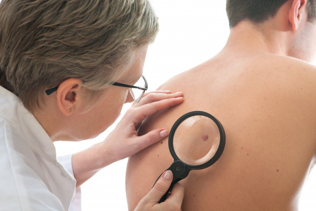 doctor inspecting patient for skin cancer