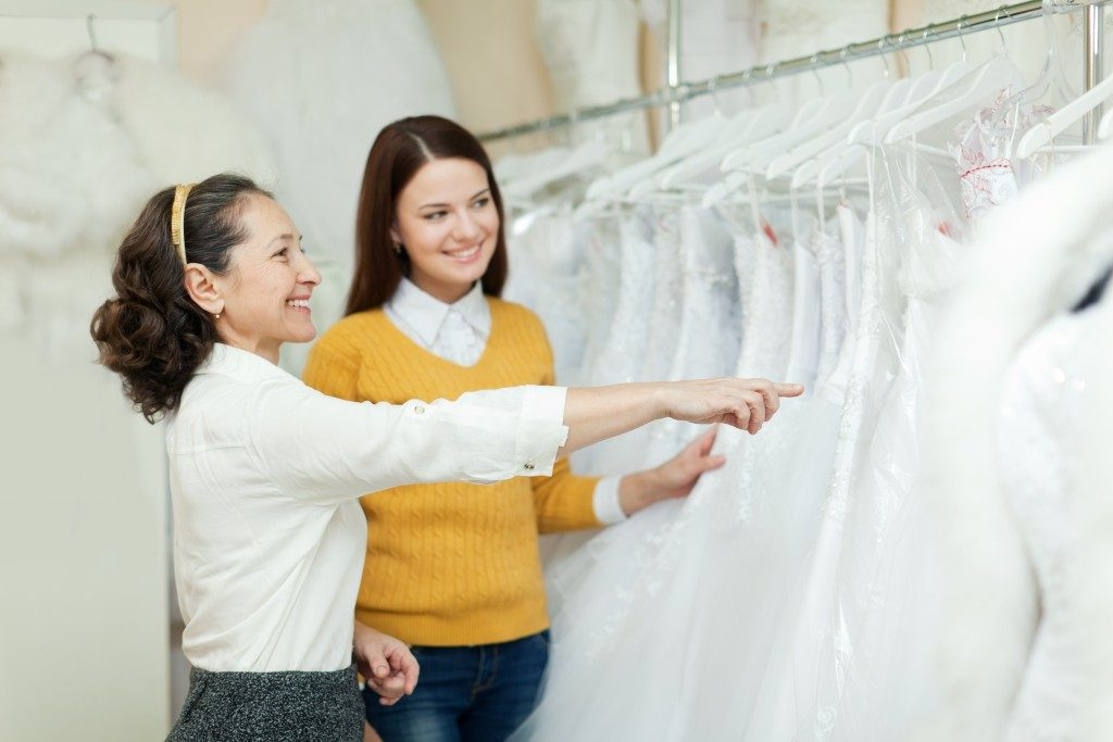 Sales lady and woman looking for a gown