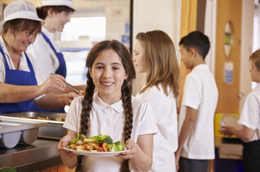 Girl holding plate of food in school cafeteria
