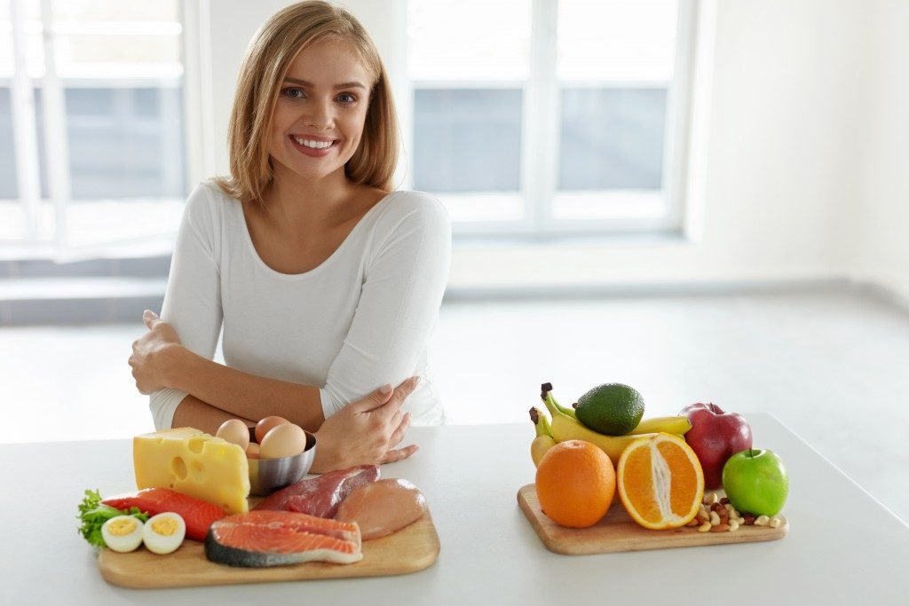 Woman sitting in the kitchen with healthy food