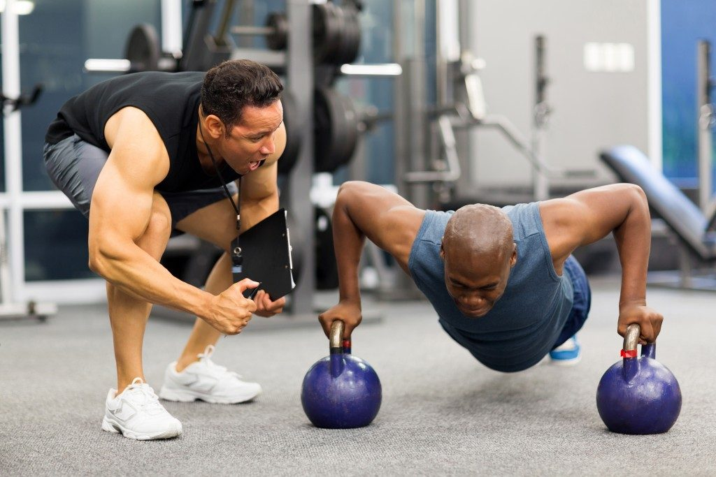 man motivating a guy working out