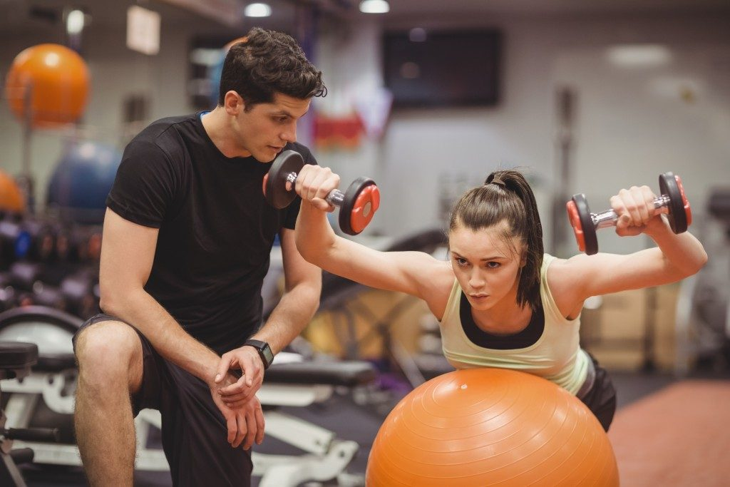 personal trainer and woman working out in the gym
