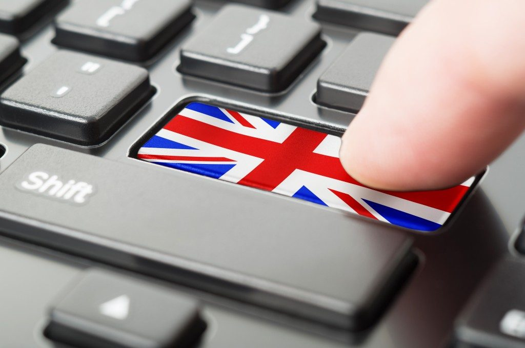 Finger pressing a UK flag on the keyboard