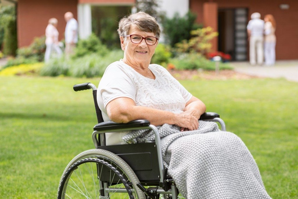 senior woman on a wheelchair in retirement home