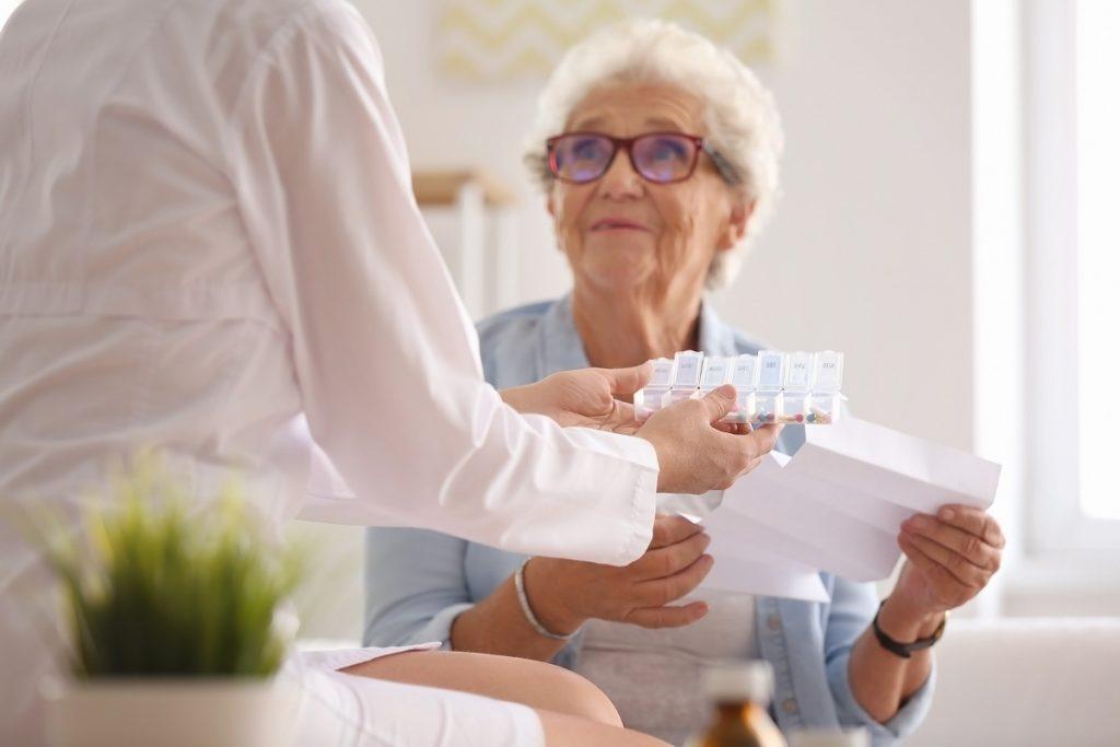 Doctor giving senior patient medicine