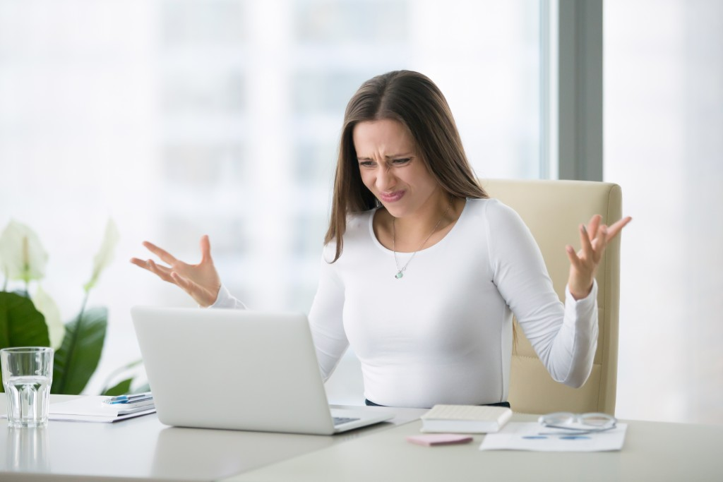 irritated woman looking at a laptop