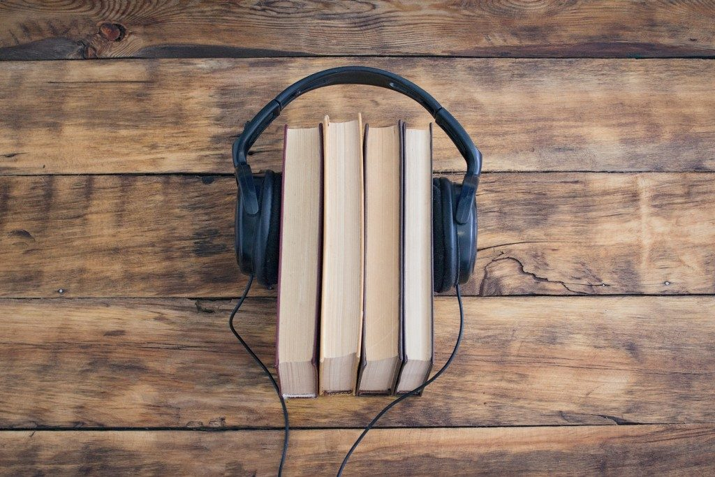 Headphones on the Pile of Books on the Wooden Table. Audiobooks. Learning through Audiobook.