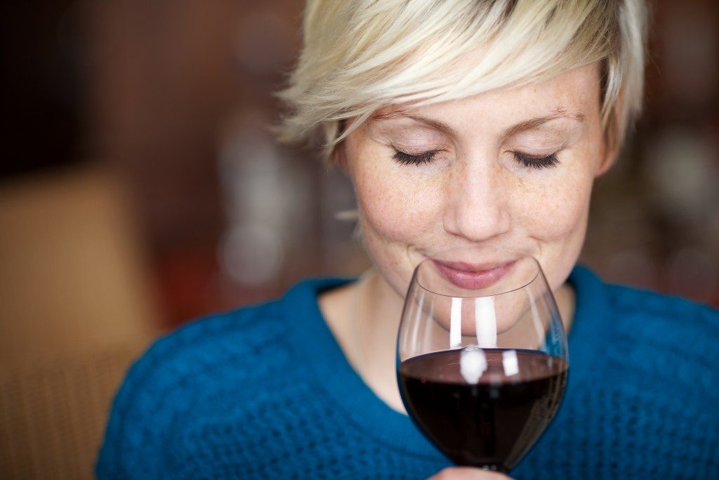 Closeup portrait of young female customer drinking red wine with eyes closed