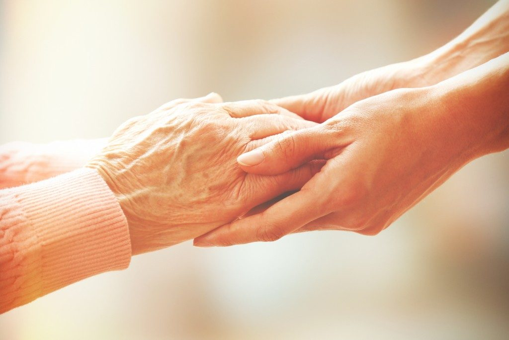 Holding an elderly woman's hand