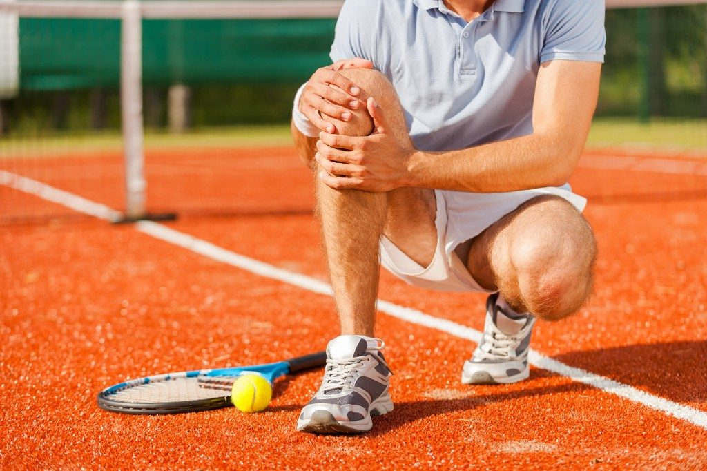Tennis player holding his knee injury
