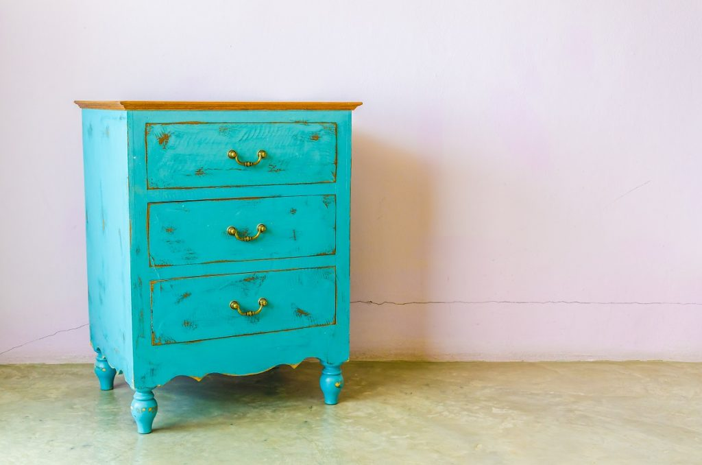 an antique cabinet in teal color and wooden top