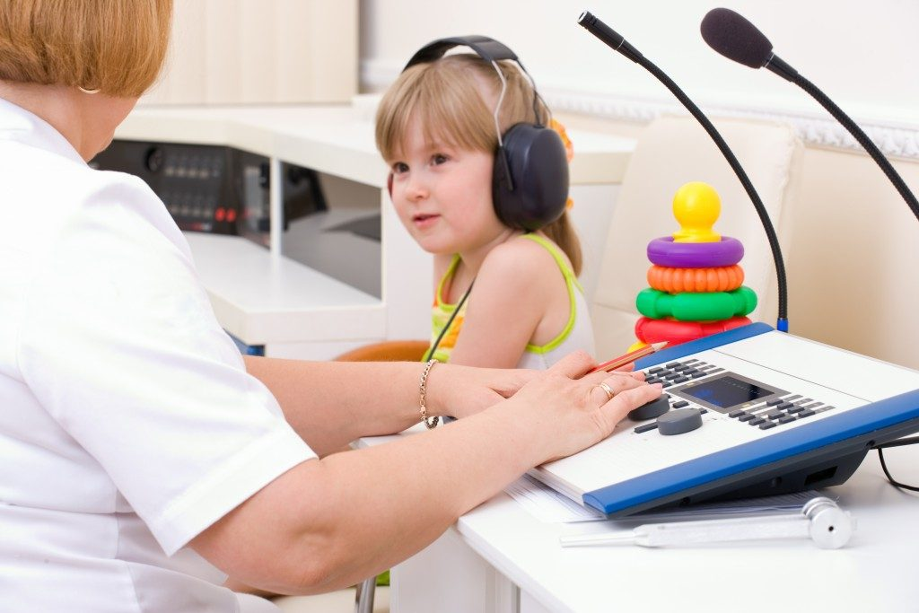 doctor testing child's audio