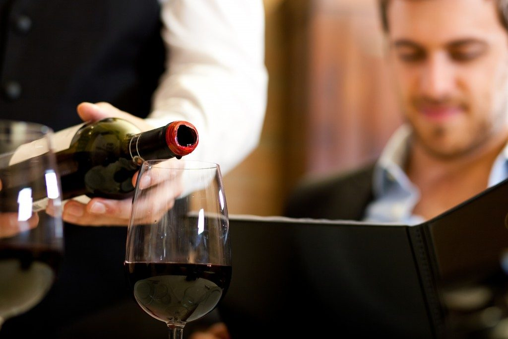 Waiter pouring red wine to a glass