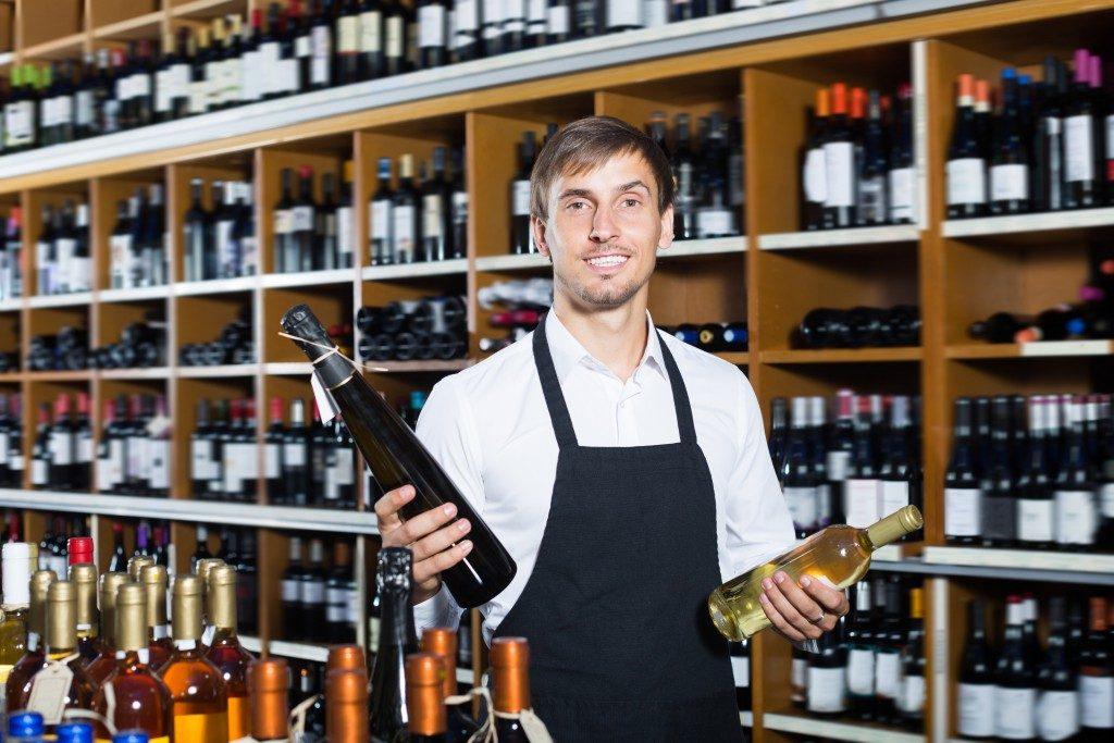 Man wearing apron selling wine