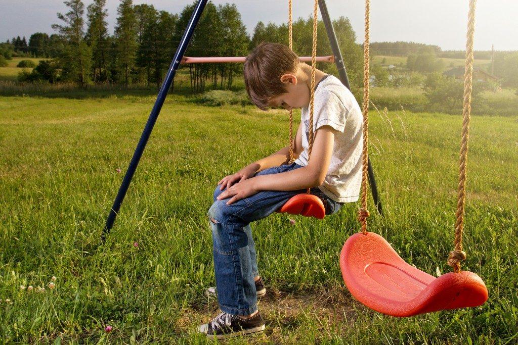 Sad kid on a swing