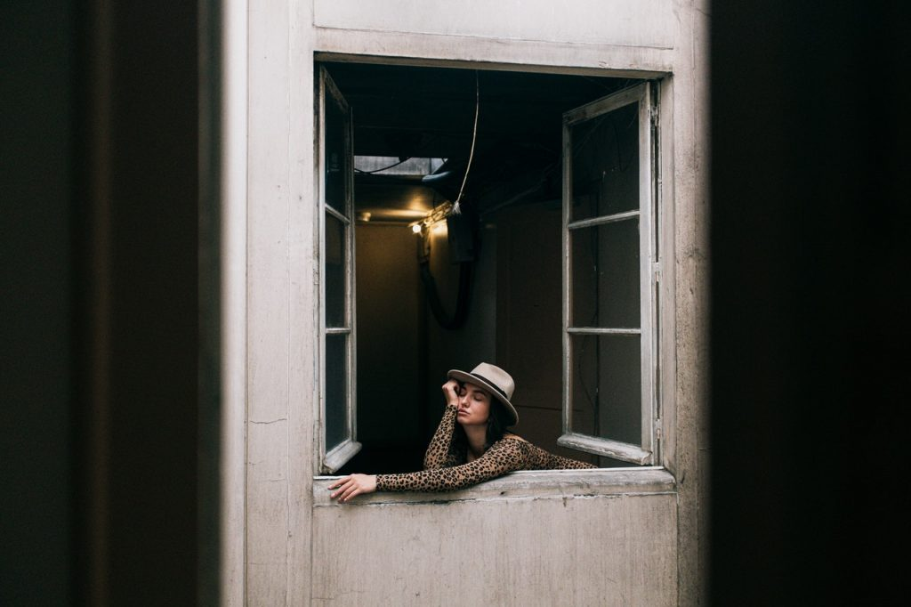 woman sticking her head out of a window due to boredom