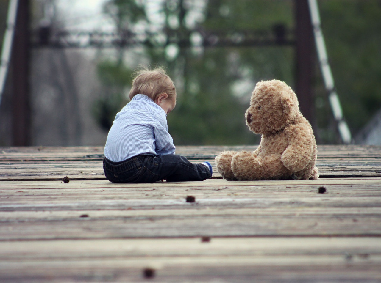 toddler sitting with teddy bear
